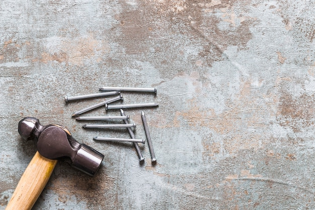 Elevated view of hammer and nails on old wooden desk Free Photo