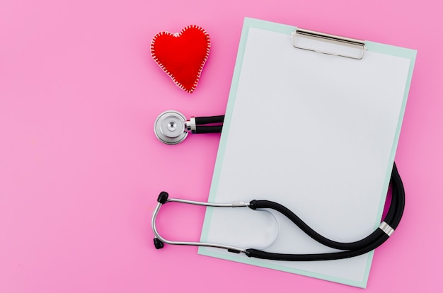 An elevated view of hand-made red heart with stethoscope and clipboard on pink background Free Photo