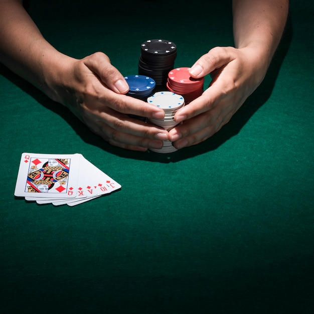 Elevated view of a hand paying poker in casino Free Photo
