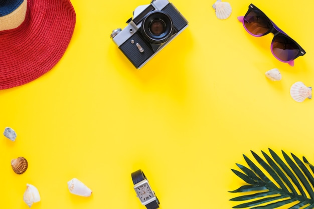 Elevated view of hat; camera; sunglasses; sea shells; wrist and palm leaf on yellow surface Free Photo
