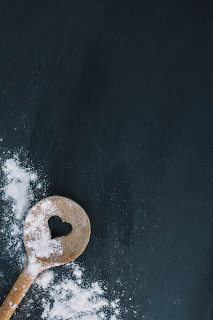 Elevated view of heart shape spoon and flour on black surface Free Photo