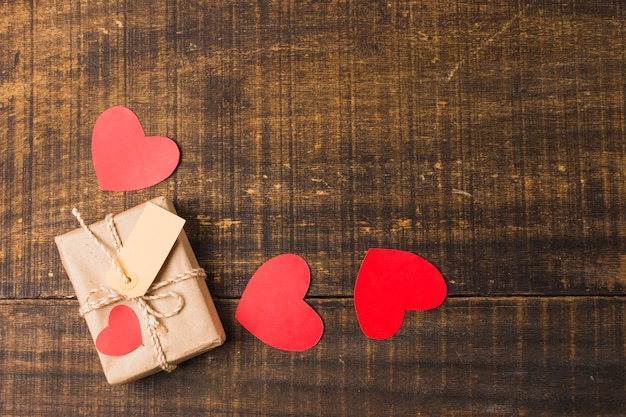 Elevated view of hearts; gift box and tag on texture panel Free Photo