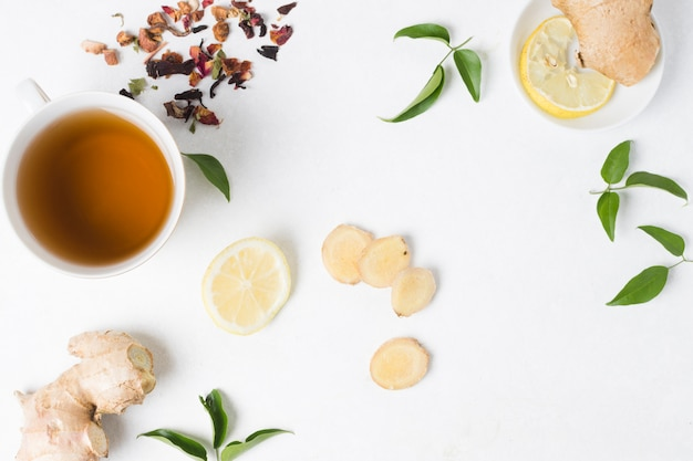 An elevated view of herbal tea cup with lemon; ginger and dried herbs on white backdrop Free Photo