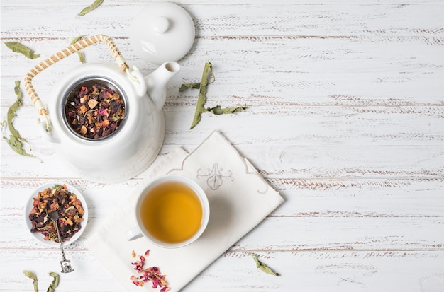 An elevated view of herbal tea and dried herbs on white wooden desk Free Photo