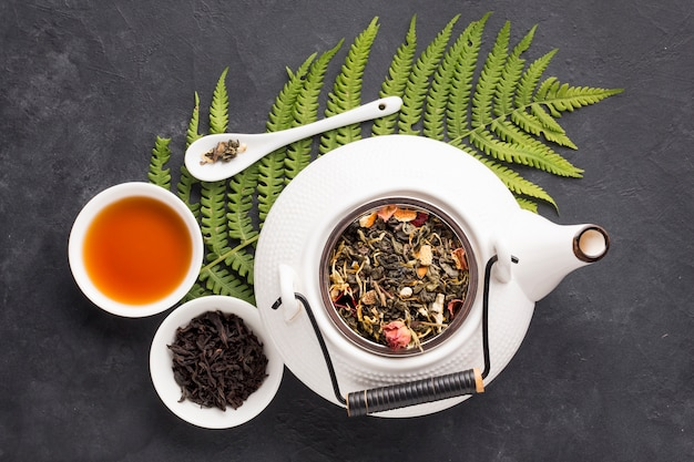Elevated view of herbal tea and healthy ingredient with fern leaf on black slate background Free Photo
