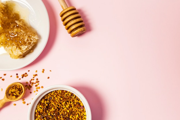 Elevated view of honeycomb and bee pollen over pink surface Free Photo