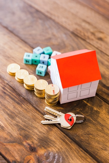 Elevated view of house model, key, math blocks and stacked coins on wooden background Premium Photo