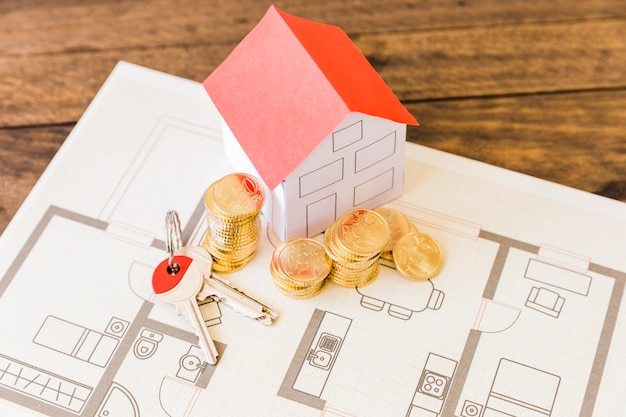 Elevated view of house model with key and stacked coins over blueprint Premium Photo