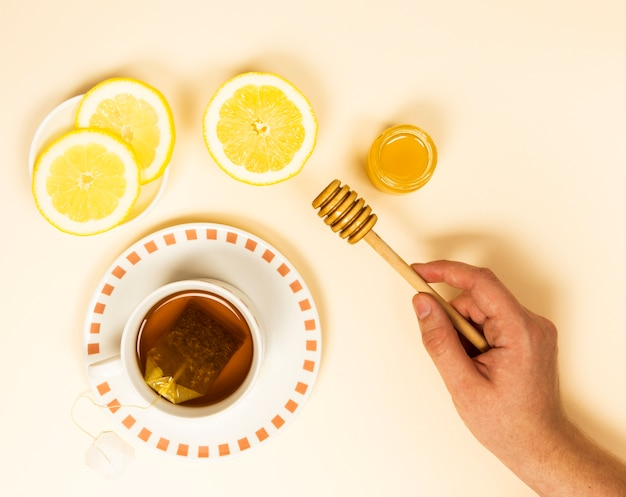 Elevated view of human hand holding honey dipper near healthy tea and lemon slice Free Photo