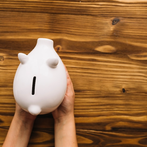 Elevated view of human hand holding piggybank over wooden desk Free Photo