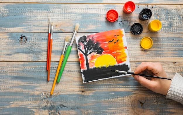 Elevated view of human hand painting sunset seen with paint brush on wooden desk Free Photo