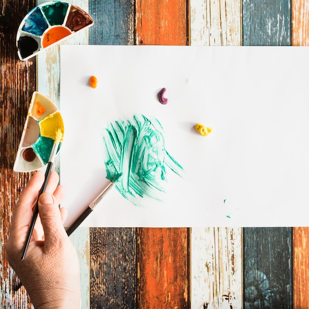 Elevated view of human hand painting on white sheet on grunge wooden background Free Photo
