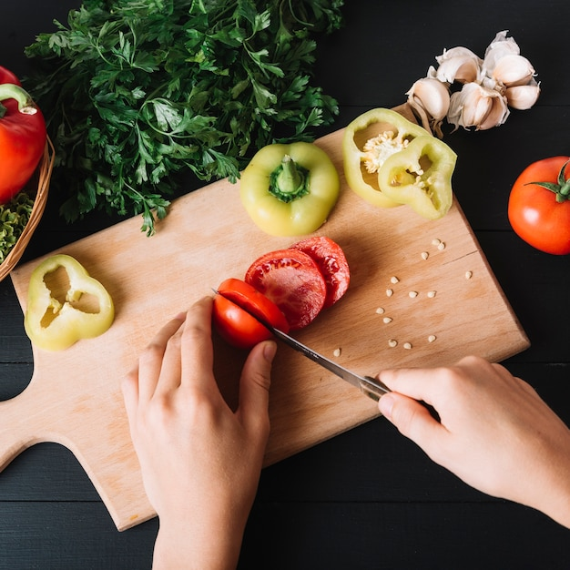 Elevated view of a human hand slicing fresh red tomato on wooden chopping board Free Photo