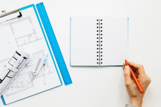 Elevated view of human hand writing on diary near blueprint clipboard Free Photo