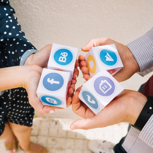 Elevated view of human hands holding blocks of mobile application icons Free Photo