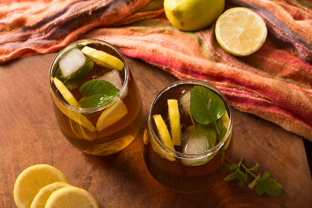 An elevated view of iced lemon tea and mint leaves on wooden table Free Photo