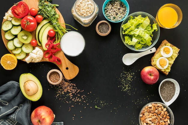 Elevated view of ingredients; dryfruits and vegetables on black background Free Photo