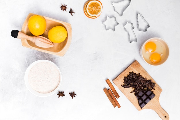 An elevated view of ingredients and pastry cutters on white textured background Free Photo