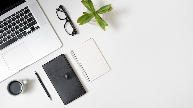 Elevated view of laptop; coffee cup; diary; eyeglasses and potted plant over business desk Free Photo