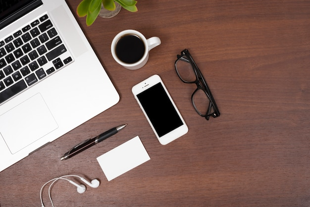 Elevated view of laptop; mobile phone; tea; earphones; pen and eye glasses on wooden table Free Photo