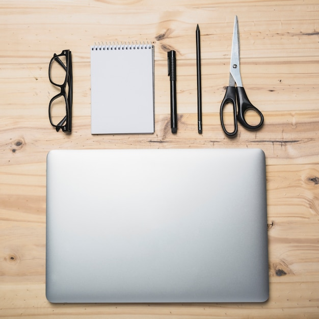 Elevated view of laptop; stationeries and spectacles on wooden background Free Photo