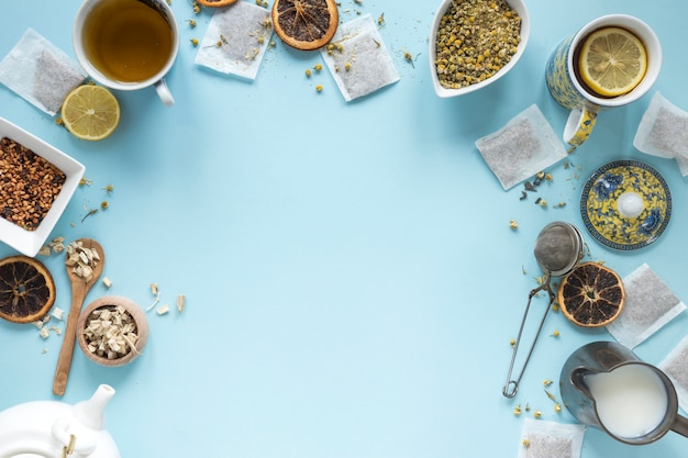 Elevated view of lemon tea; herbs; milk; strainer; dried chinese chrysanthemum flowers; teapot and teabags arranged on blue background Free Photo