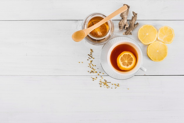 Elevated view of lemon tea; honey and ginger on wooden backdrop Free Photo