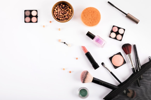 Elevated view of makeup brushes and cosmetics on white backdrop Free Photo