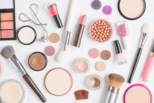 Elevated view of makeup kits on white backdrop Free Photo