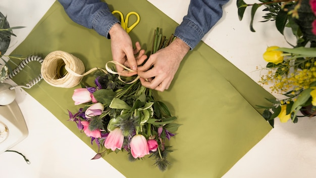 An elevated view of male tourist tying the flower bouquet with string on green paper over the desk Free Photo