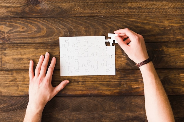 Elevated view of man solving jigsaw puzzle over wooden table Free Photo