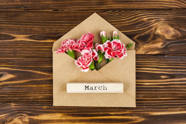 Elevated view of march text on wooden block over envelope with red flowers Free Photo
