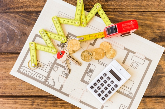 Elevated view of measure tape, stacked coins, key and calculator on blueprint Free Photo