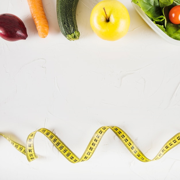 Elevated view of measuring tape and healthy food on white background Free Photo