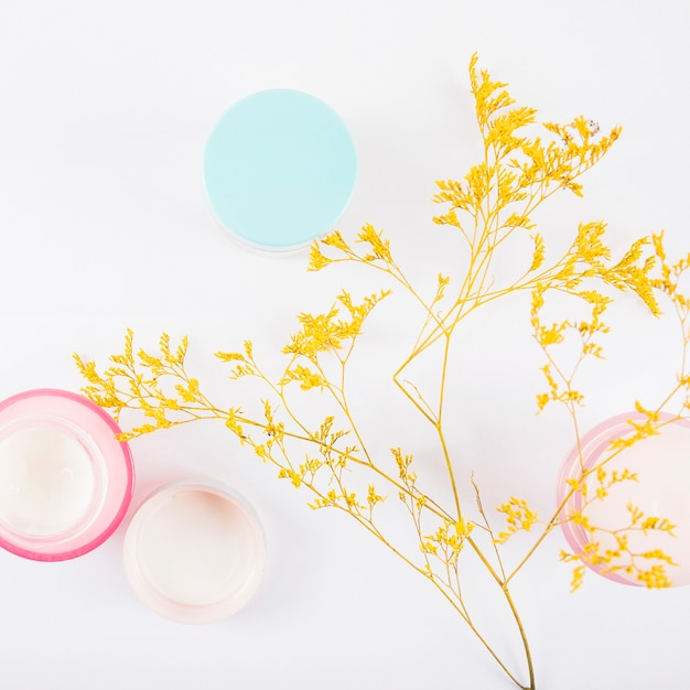 Elevated view of moisturizing creams and yellow flowers on white backdrop Free Photo