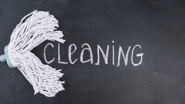 Elevated view of mop head with cleaning text on blackboard Free Photo