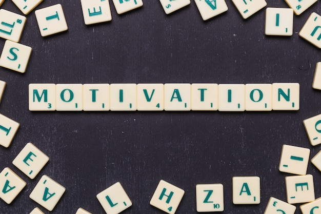 Elevated view of motivation word made from game scrabble letters Free Photo