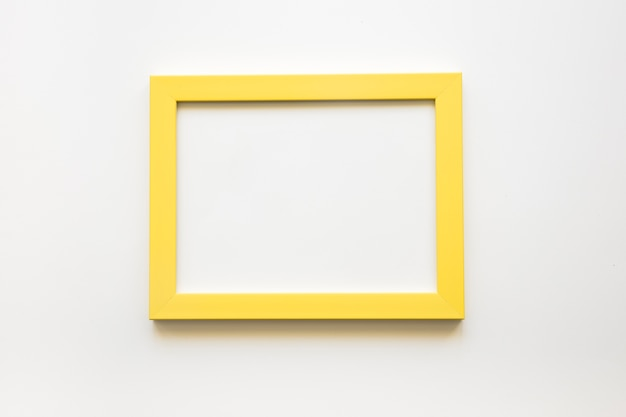 Elevated view of blank yellow frame on white background Photo | Free ...