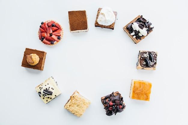 Повышенный вид на вкусные пирожные формирования кадра на белом фоне Premium Фотографии