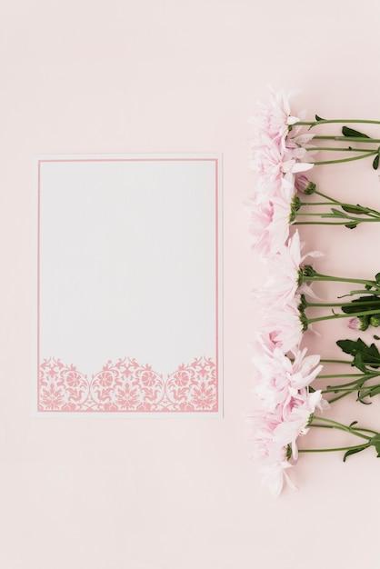 ピンクの背景に花とデザインされたホワイトペーパーの立面図 無料写真