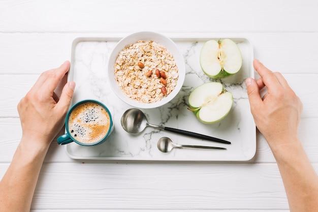 白い背景の上においしい食事のトレイを保持している人間の手の立面図 無料写真