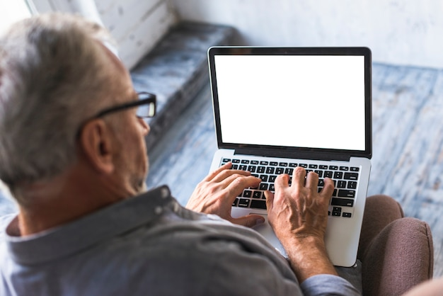 Elevated view of man using laptop with white blank screen Free Photo