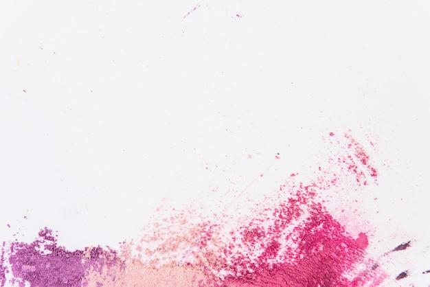 Повышенный вид разноцветной косметической пудры на белом фоне Premium Фотографии