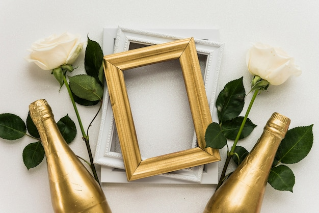 Elevated View Of Picture Frames With Two Roses And Champagne Bottle