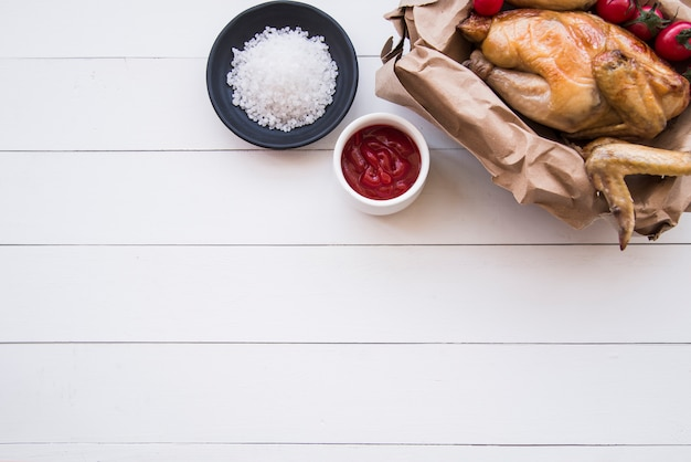Elevated view of roasted chicken; tomato sauce and salt on white wooden table Free Photo