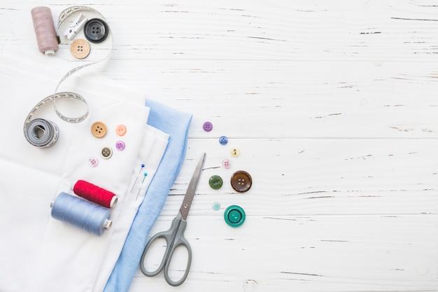 Повышенный вид текстиля с швейными изделиями на деревянном фоне Premium Фотографии
