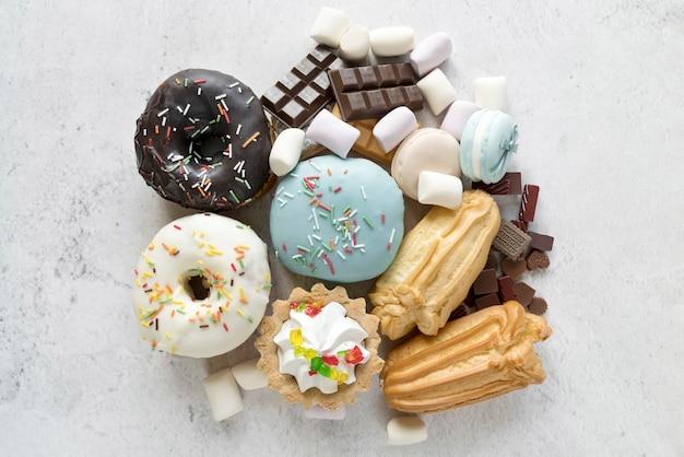 白いセメント織り目加工の背景に様々な菓子食品の立面図 無料写真