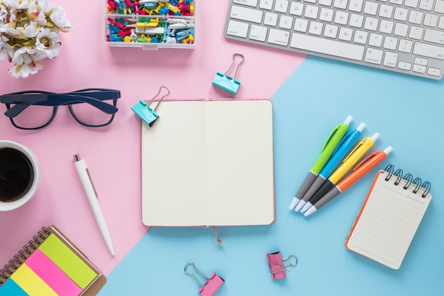 An elevated view of office supplies on dual pink and blue background Free Photo