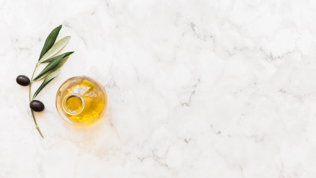 Elevated view of olive oil bottle with twig on marble background Free Photo
