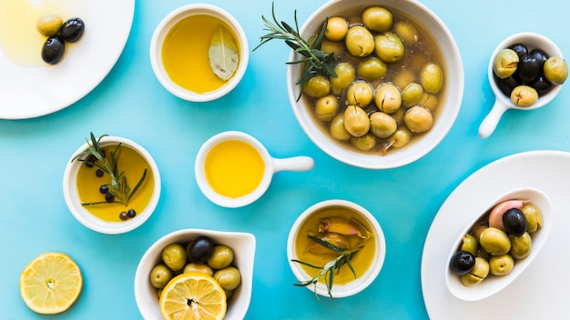 Elevated view of olive oil in different container on blue backdrop Free Photo